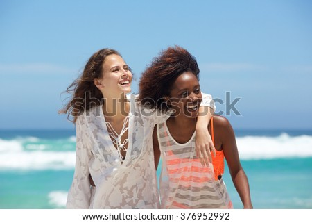 Close up portrait of two carefree young women at the beach