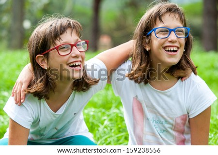 Close up portrait of two disabled twin sisters outdoors. - stock photo