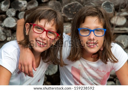 Close up portrait of two disabled twin sisters smiling.