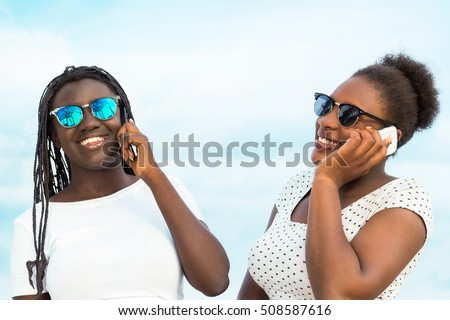 Close up portrait of two diverse african teen girls wearing sun glasses talking on smart phones outdoors.