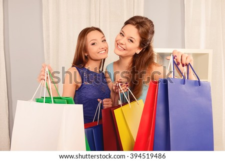 Close up portrait of two happy girls with shopping packs - stock photo