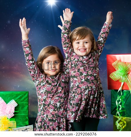 Close up portrait of two happy young sisters raising hands next to gifts. Studio portrait with winter background. - stock photo