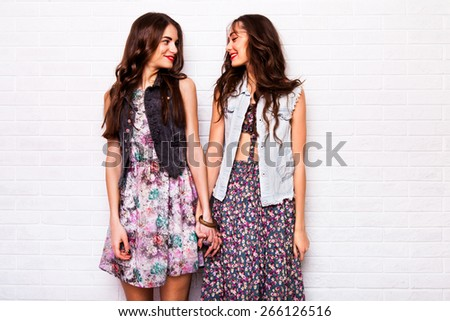 Close up portrait of two pretty hipster best  friends wearing boho colorful dress, stylish jacket and baubles. Girls smile, have fun against urban white wall. - stock photo