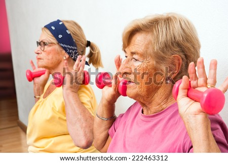 Close up portrait of two senior women doing exercise with weights in health club.