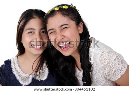 Close up portrait of two two beautiful Asian girls with bright smiles pose to camera, isolated on white background - stock photo