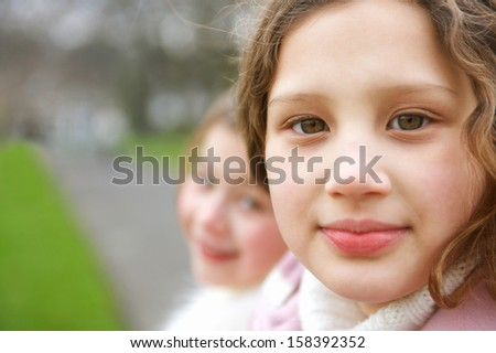 Close up portrait of two young girls children sisters sitting together in a park during a cold winter day, turning to the camera and smiling softly, outdoors. - stock photo