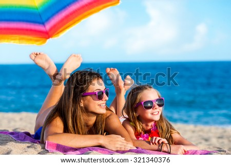 Close up portrait of two young girls laying together on beach. Young women wearing fun purple eye wear.  - stock photo