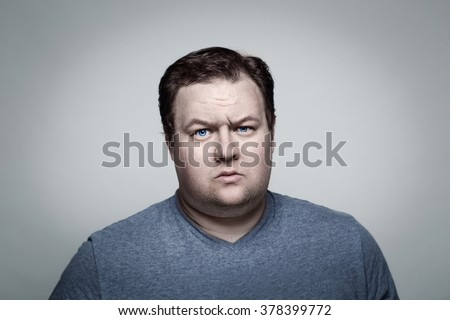 Close-up portrait of white Caucasian big fat stout man with blue eyes looking directly in camera in studio on light background, skeptical suspicious expression, emotion  - stock photo