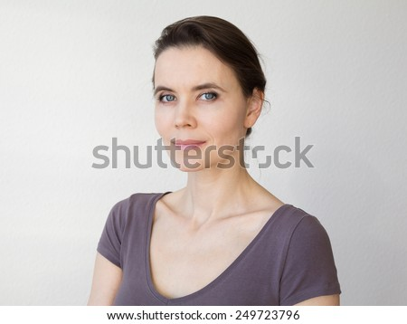 Close-up portrait of woman 30-40 years old looking into camera - stock photo