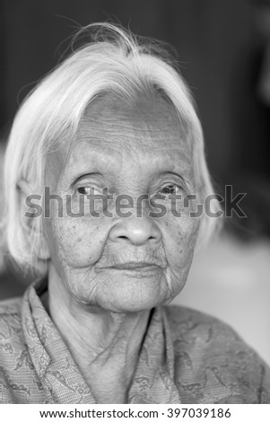 Close up portrait of 80 years old Thai woman in black and white