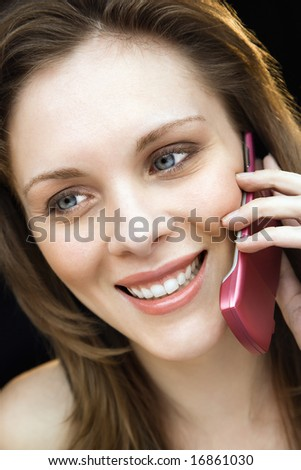 Close up portrait of young adult female talking on mobile phone and smiling.