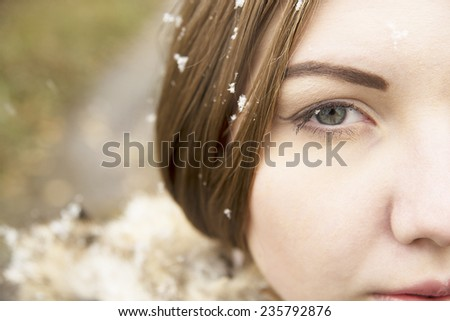 Close up portrait of Young adult girl or woman with snowflakes on long dark eyelashes, brown hair and cute face  outdoors in winter. Good weather outside Empty copy space for inscription  - stock photo