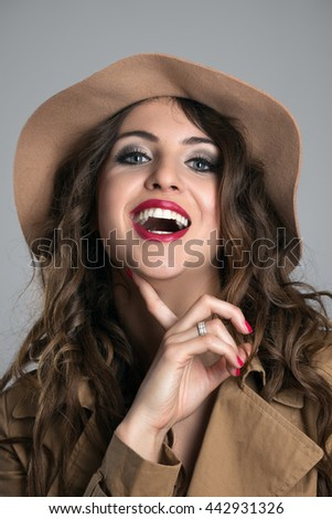 Close up portrait of young adult woman laughing with finger under her chin over gray studio background