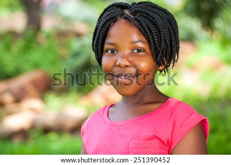 Close up portrait of young African girl with braided hairstyle outdoors in park. - stock photo
