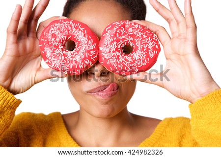 Close up portrait of young african woman sticking out her tongue and covering eyes with donuts on white background - stock photo