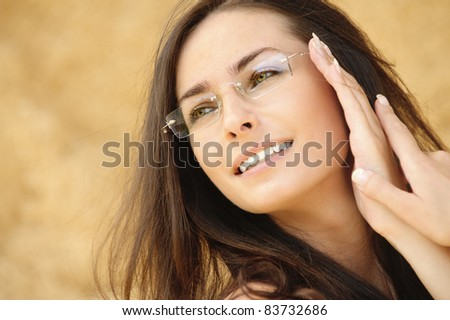 Close-up portrait of young alluring woman wearing eyeglasses against beige background. - stock photo
