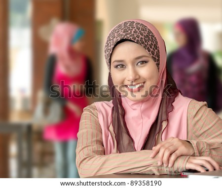Close-up portrait of young Asian Muslim girl smiles