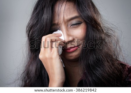 Close up portrait of young Asian woman cries in despair and wipes the tears in her eyes, over grey background - stock photo