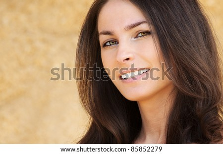Close-up portrait of young attractive brunette smiling woman looking against yellow background. - stock photo