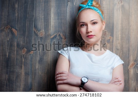 Close up portrait of young attractive confident woman looking at camera leaning on wooden wall. - stock photo