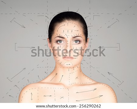 Close-up portrait of young, beautiful and healthy woman ready for plastic surgery treatment (collage with drawing arrows) - stock photo