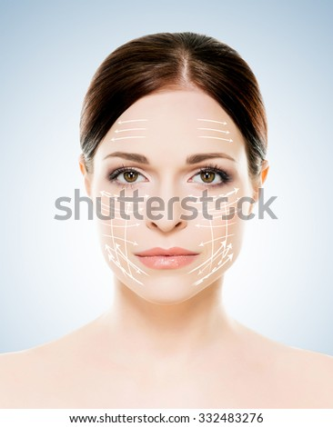 Close-up portrait of young, beautiful and healthy woman with arrows on her face (spa, surgery, face lifting and make-up concept) - stock photo