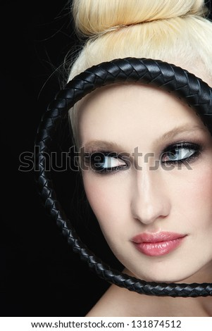Close-up portrait of young beautiful blond woman with braided bull whip - stock photo