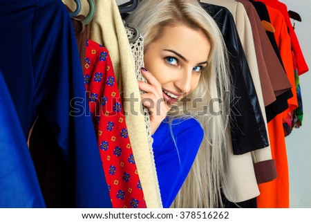 Close up portrait of young beautiful blonde in clothing store. Happy young lady with a lot of clothes. Shopping concept. - stock photo