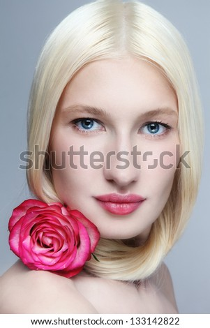 Close-up portrait of young beautiful blonde woman with pink rose - stock photo
