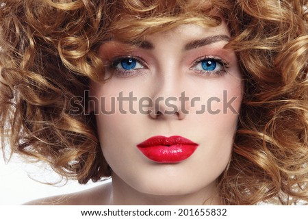 Close-up portrait of young beautiful blue-eyed woman with curly hair - stock photo