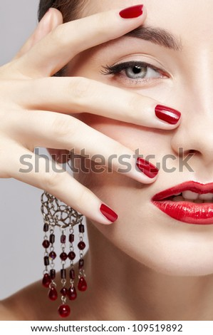 close-up portrait of young beautiful brunette woman in ear-rings touching her face with manicured hand - stock photo