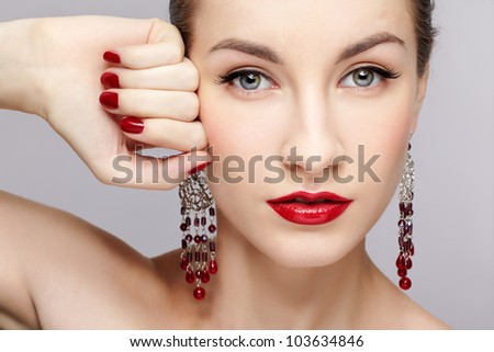 close-up portrait of young beautiful brunette woman in ear-rings touching her temple with manicured hand - stock photo