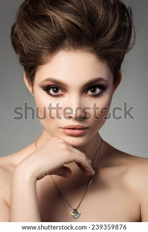 Close-up portrait of young beautiful brunette woman touching her face with heart shaped crystal pendant - stock photo