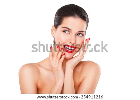 close-up portrait of young beautiful brunette woman touching her face with manicured hand - stock photo