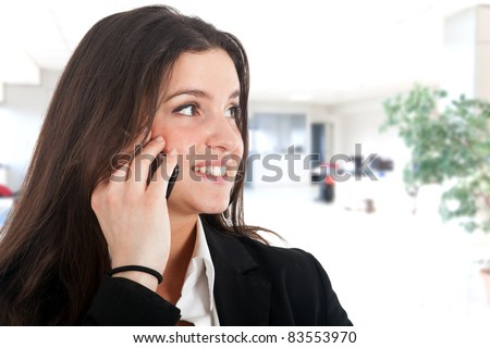 Close-up portrait of young beautiful business woman using her cell phone - stock photo