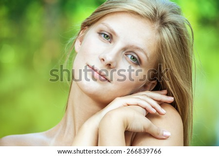 close-up portrait of young beautiful charming blond woman in green park - stock photo
