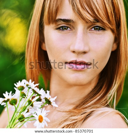 Close-up portrait of young beautiful fair-haired woman with bouquet of camomiles at summer green park. - stock photo