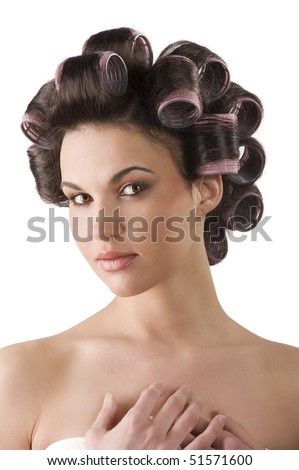 close up portrait of Young beautiful girl having hair curlers on her head isolated on white background - stock photo