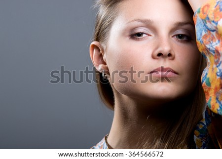 Close-up portrait of young beautiful girl in a bright colored blouse on a gray background looking at the camera. - stock photo