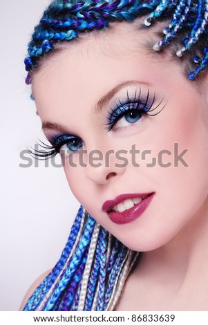 Close-up portrait of young beautiful girl with fancy blue hairstyle and extra long fake eyelashes - stock photo