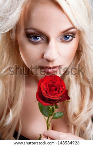 Close-up portrait of young beautiful sexy blond woman with red rose. - stock photo