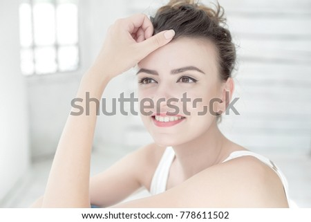 Close-up portrait of young beautiful smiling brunette woman wearing white singlet in white bright room background