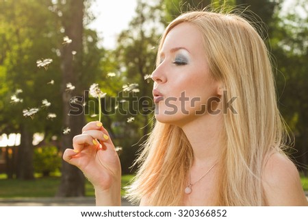 Close up portrait of young beautiful woman blowing  on a dandelion.