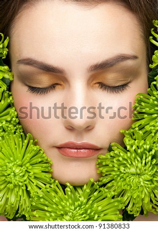 Close-up portrait of young beautiful woman face with stylish makeup surrounded green flowers - stock photo
