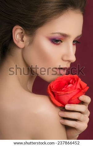 Close-up portrait of young beautiful woman holding red rose. Spa concept.