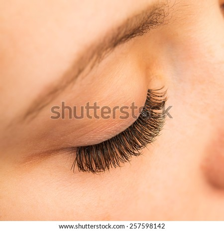 close-up portrait of young beautiful woman's closed, eye zone make up with black arrow - stock photo