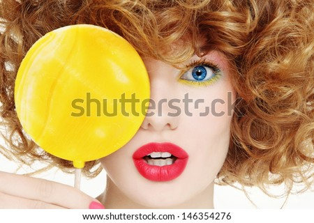 Close-up portrait of young beautiful woman with bright make-up and big yellow lollipop - stock photo