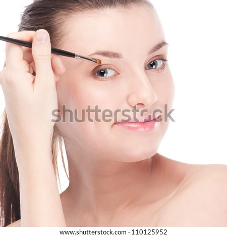 Close-up portrait of young beautiful woman with brush for make-up. Eye shadow zone - stock photo
