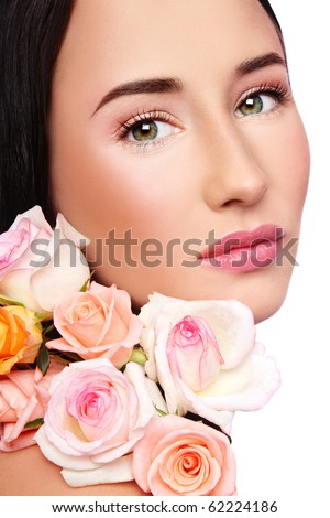 Close-up portrait of young beautiful woman with clear make-up and fresh tender roses