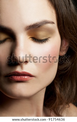 Close-up portrait of young beautiful woman with closed eyes with stylish make-up - stock photo